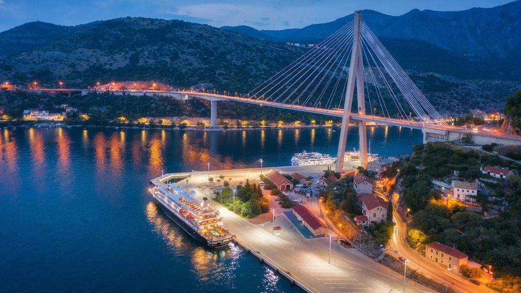 Aerial view of cruise ship at harbor and beautiful bridge at night. Landscape with ships and boats in harbour, city illumination, road, mountains, blue sea at sunset. Top view. Floating liner in port