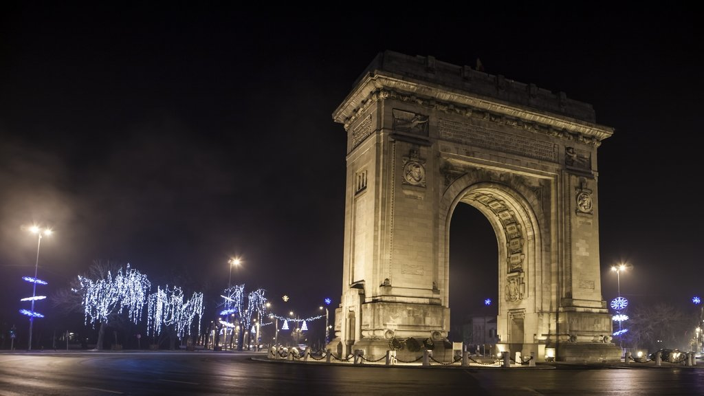 Arc de triomphe in a boulevard bucharest romania at night with lights